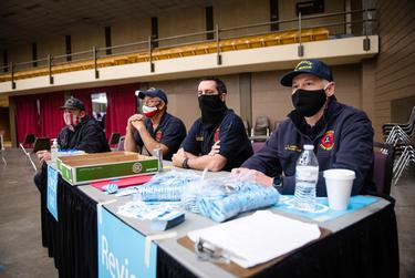 Firefighters wait to check people out of a vaccination site in the Lubbock Memorial Civic Center on April 14, 2021.