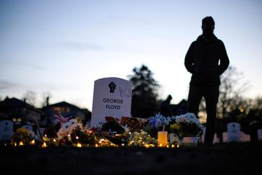 """A person stands at the """"Say Their Names"""" cemetery on the day of the guilty verdict in the trial of former Minneapolis police officer Derek Chauvin, at George Floyd Square in Minneapolis, Minnesota, on April 20, 2021."""