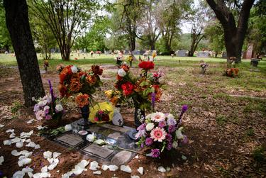 Flowers adorn the graveside of Michael Ramos at Assumption Cemetery in Austin, on April 19, 2021.  Ramos was shot and killed by Austin police officer Christopher Taylor last year while exiting a parking space.