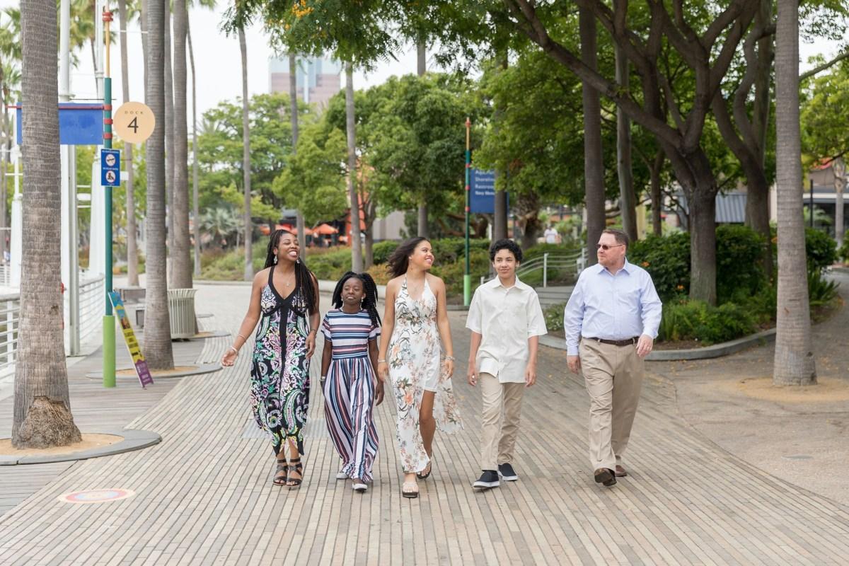 Family of five walking side by side.