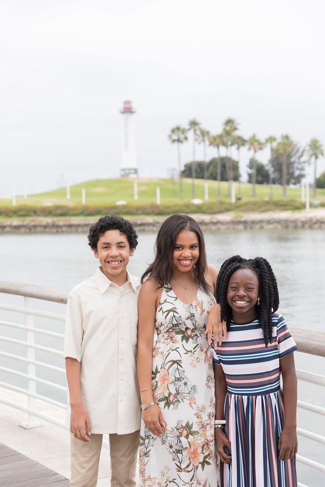 Three children standing on a bridge, smiling.