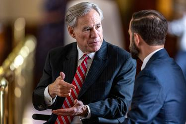 Gov. Greg Abbott speaks with lawmakers on the House floor during the legislative session on Sunday, May 23, 2021.