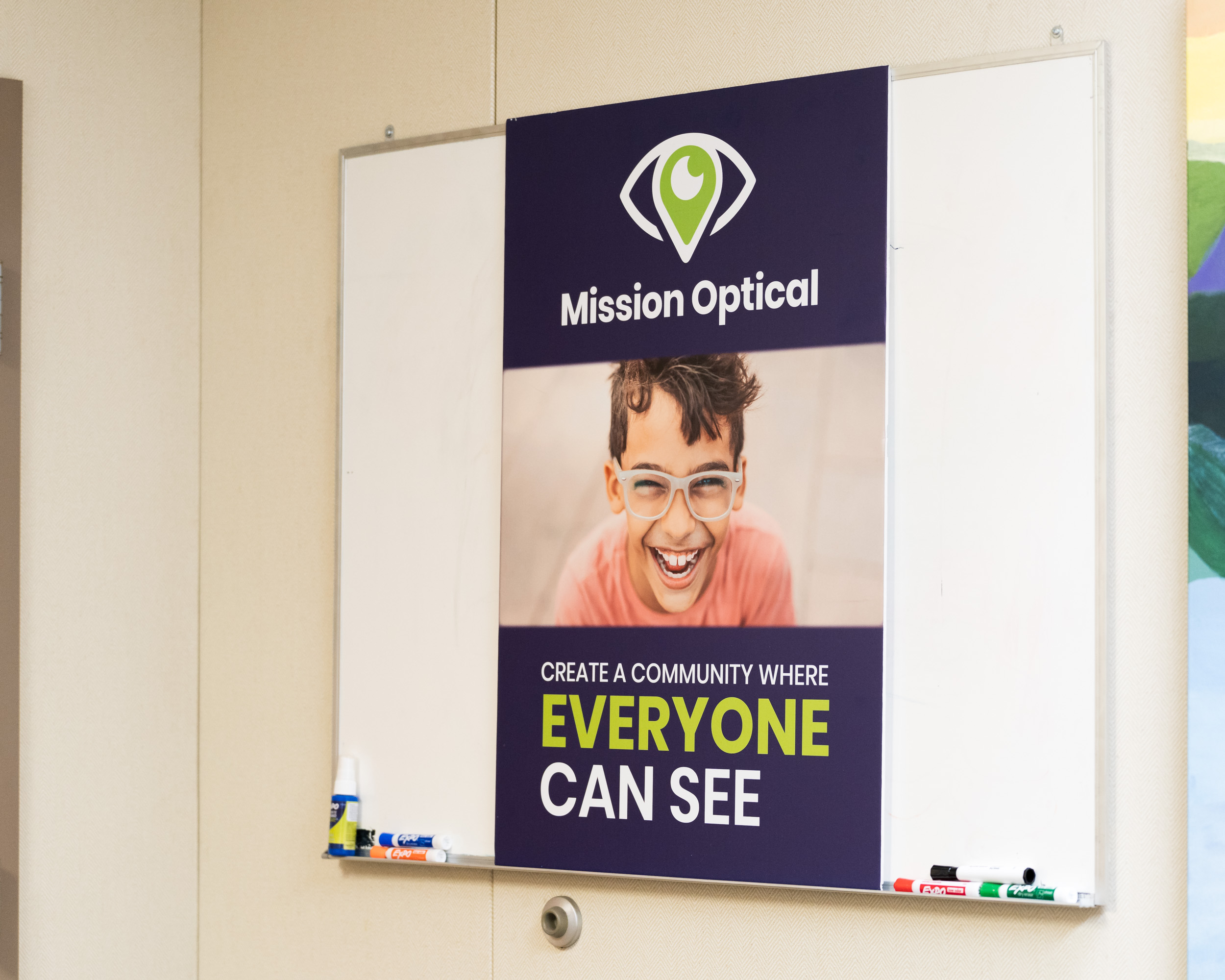 A 'Mission Optical' poster on a white board.