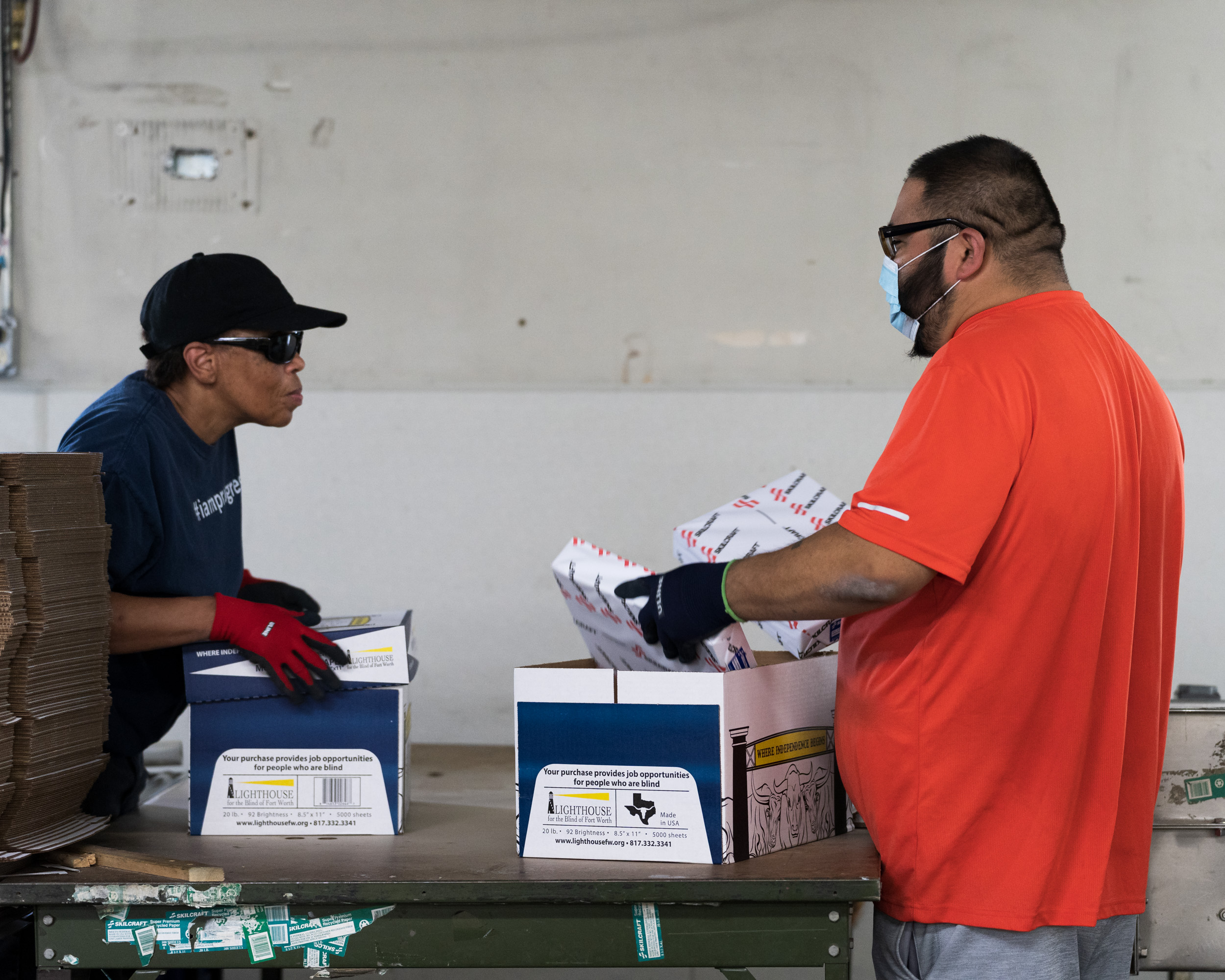 Two workers talk to each other while filling boxes with paper