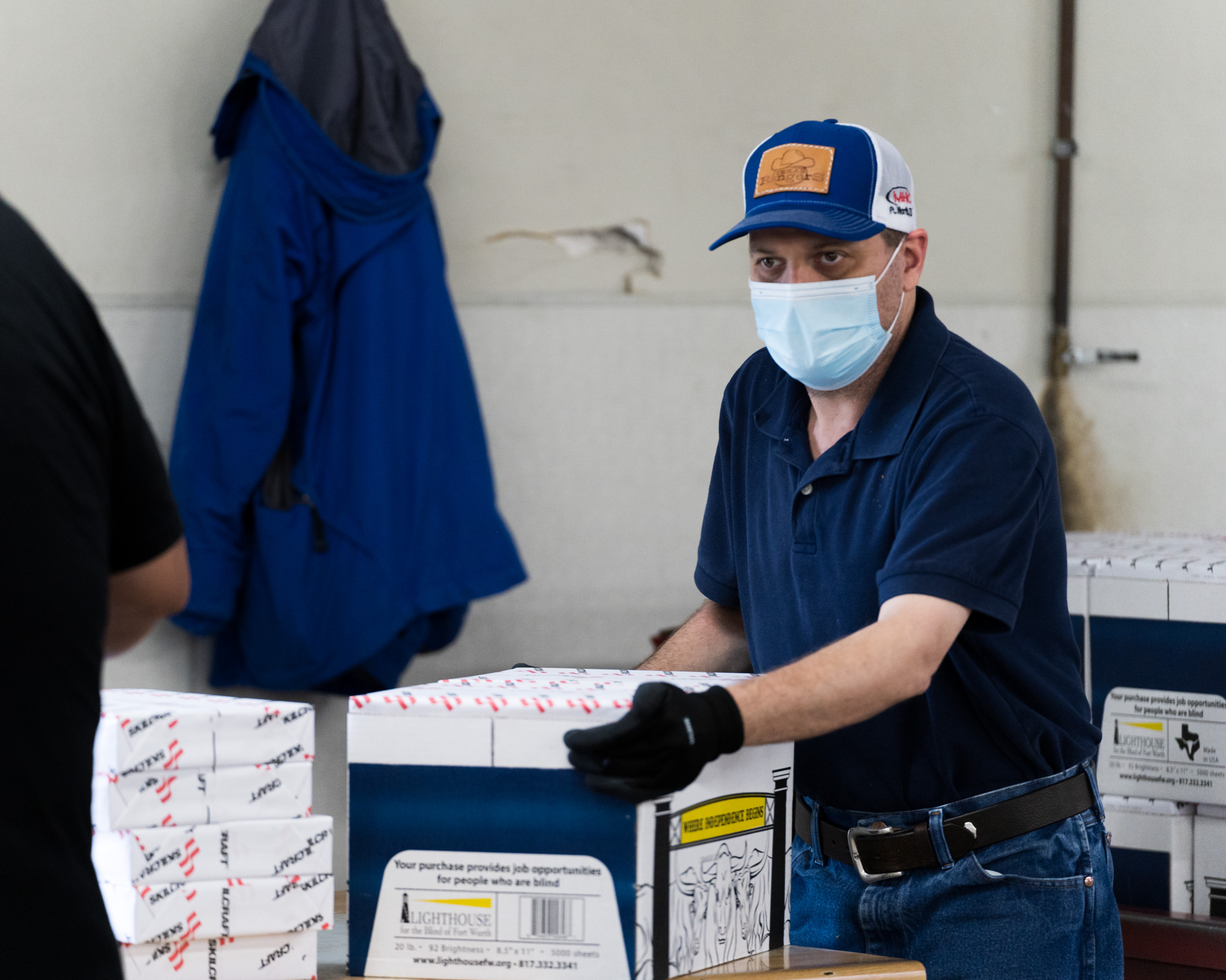 A man with a mask and hat on moves boxes filled with paper