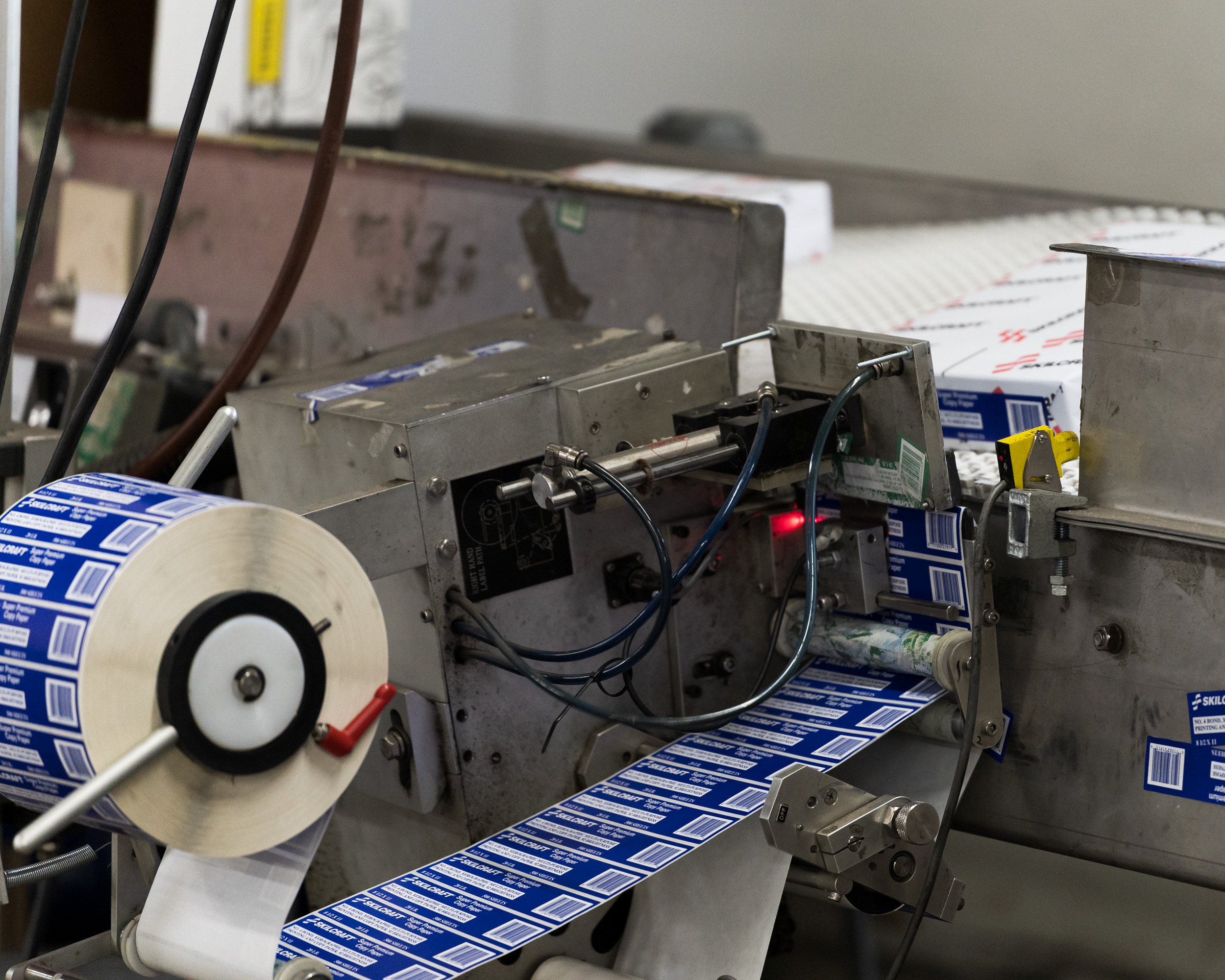 A machine stickers stacks of paper