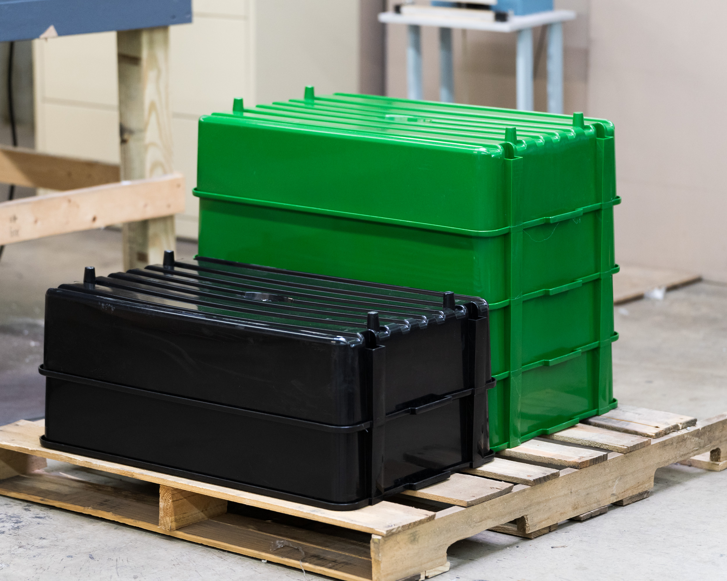 Black and green containers stacked on a pallet