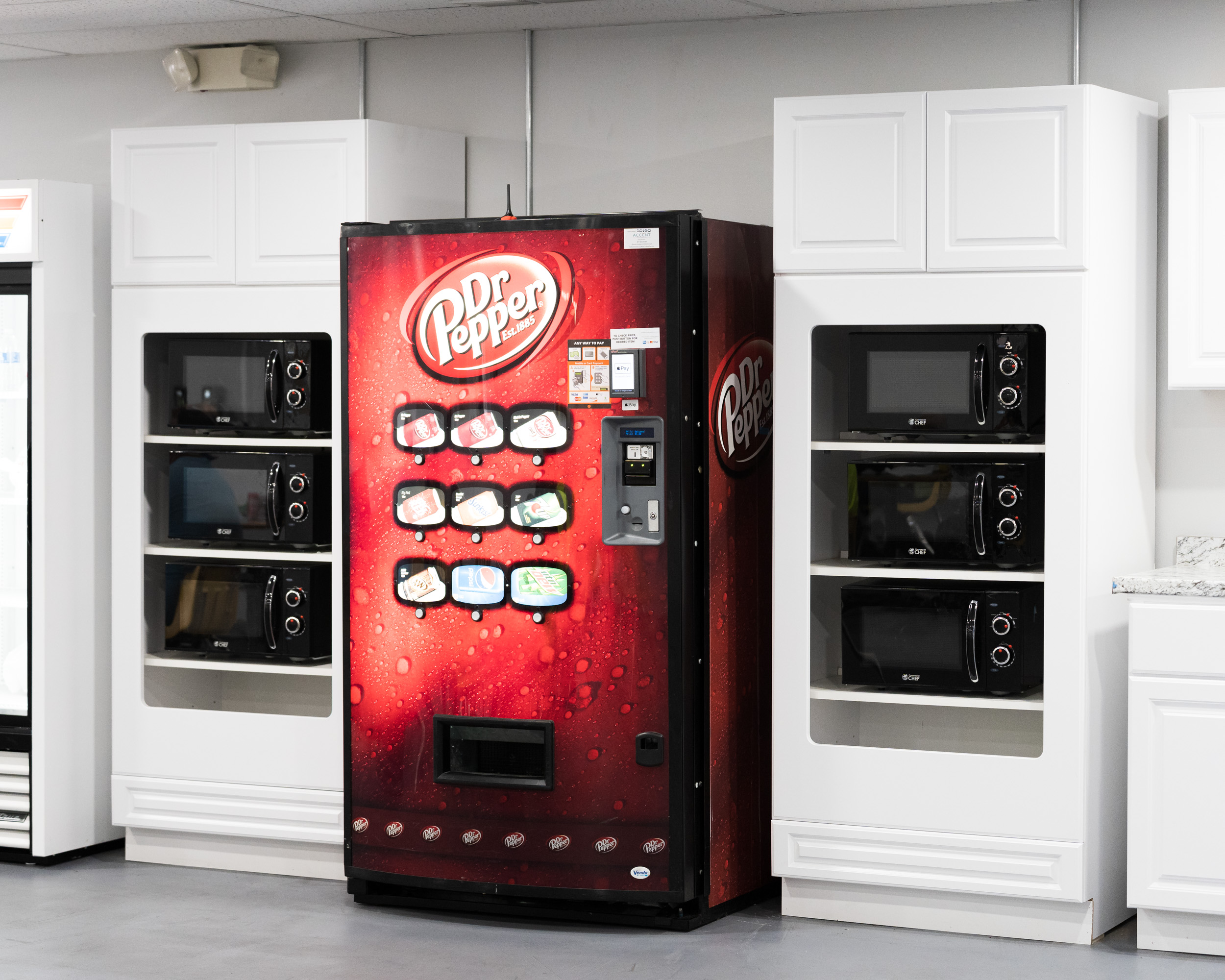A red soda dispensing machine with six black microwaves next to it