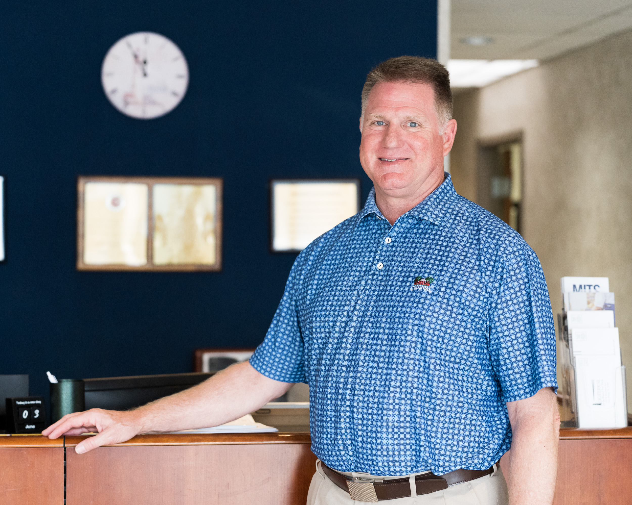 A man with a blue shirt standing in front of a desk
