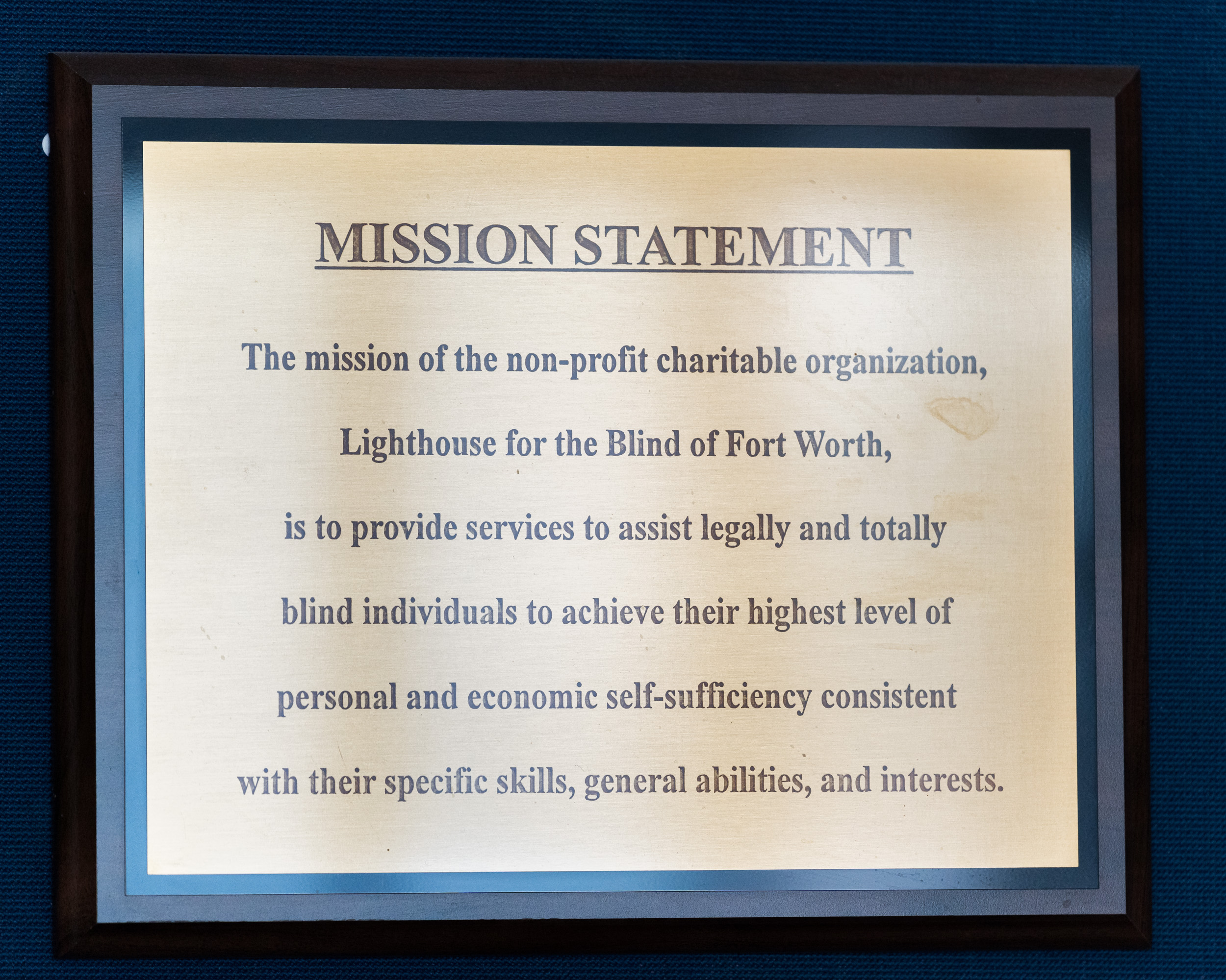 """A plaque that says: """"Mission Statement. The mission of the non-profit charitable organization, Lighthouse for the Blind of Fort Worth, is to provide services to assist legally and totally blind individuals to achieve their highest level of personal and economic self-sufficiency consistent with their specific skills, general abilities, and interests."""""""