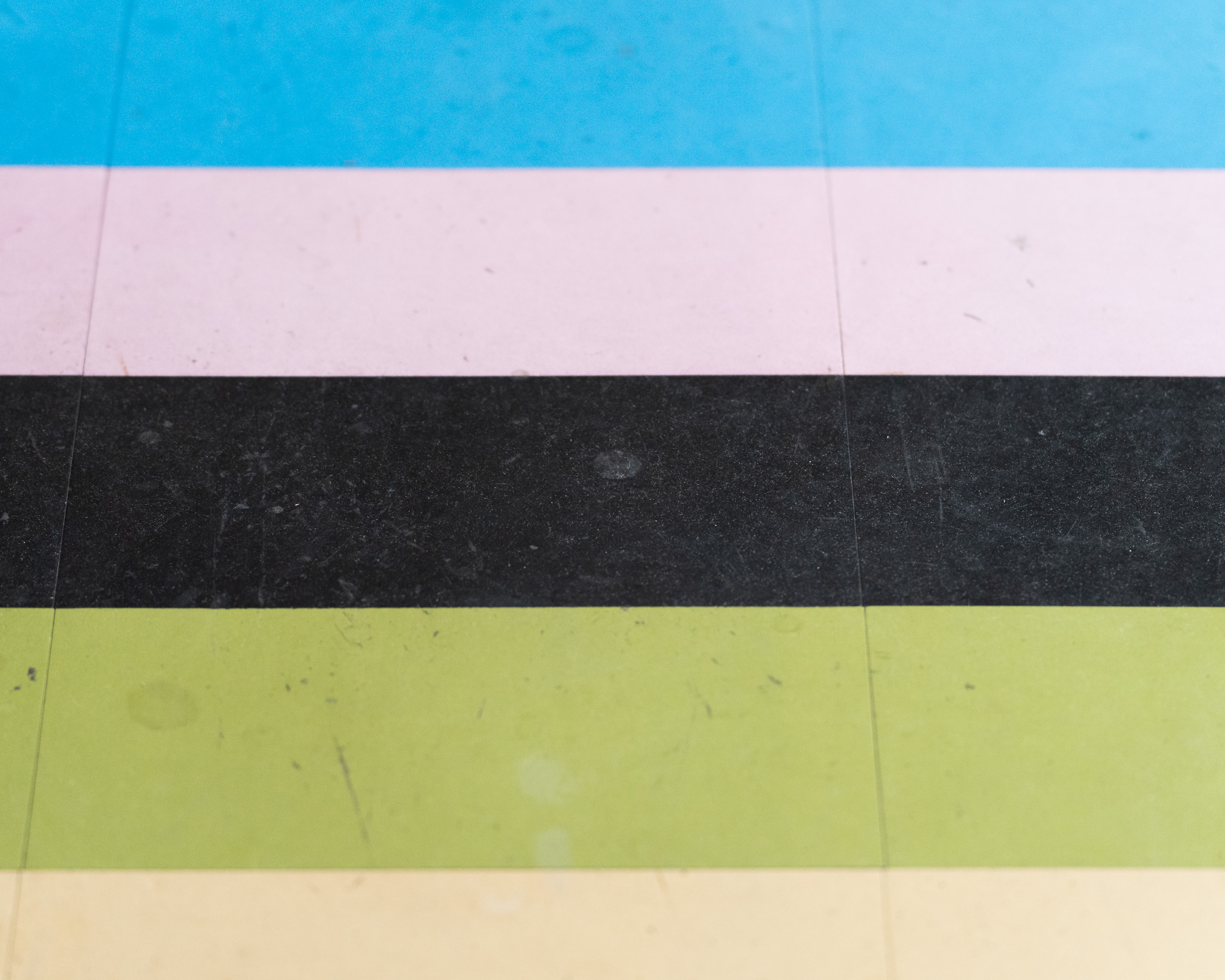 A black, green, pink and blue line on the floor
