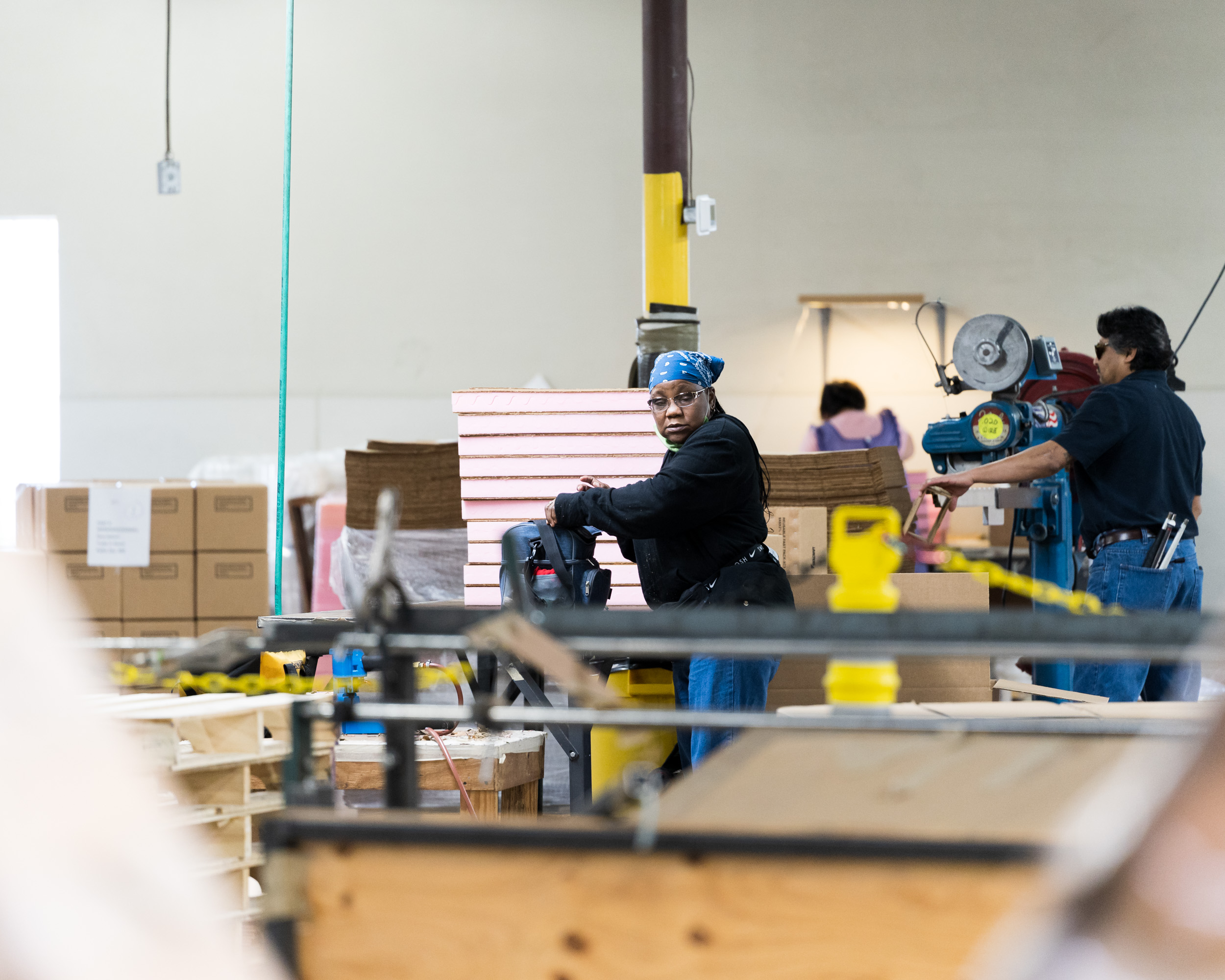 Workers using machinery in a warehouse