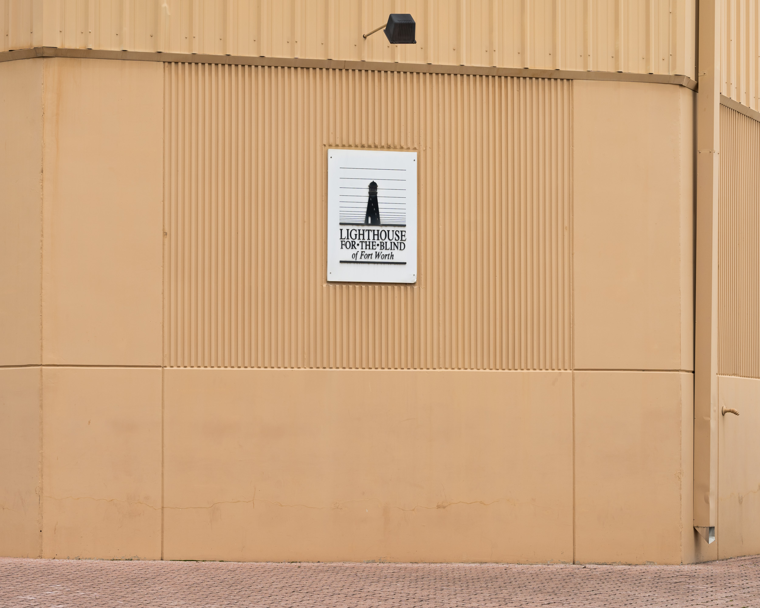 A brown wall with the Lighthouse for the Blind of Fort Worth logo