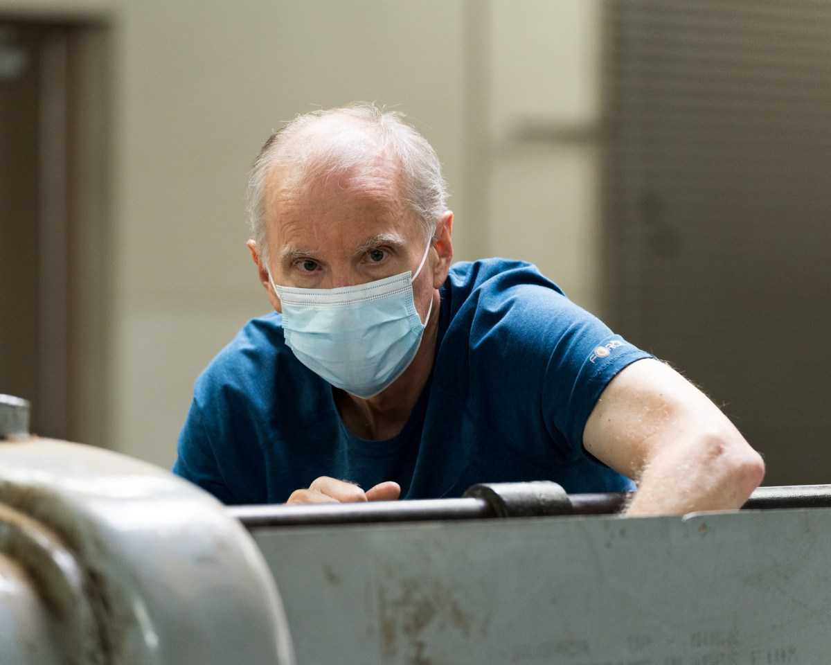 A man with a mask on cleaning a machine