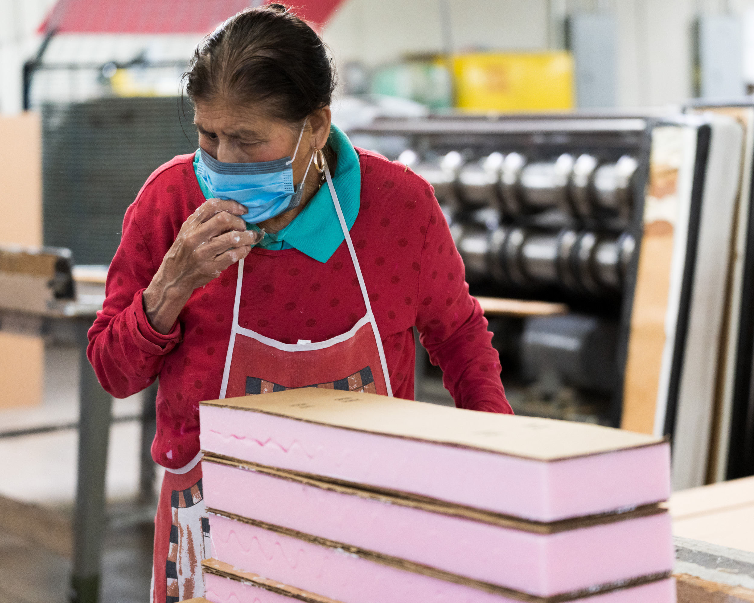 A woman with a mask on walking away from pink foam pads stacked on top of each other