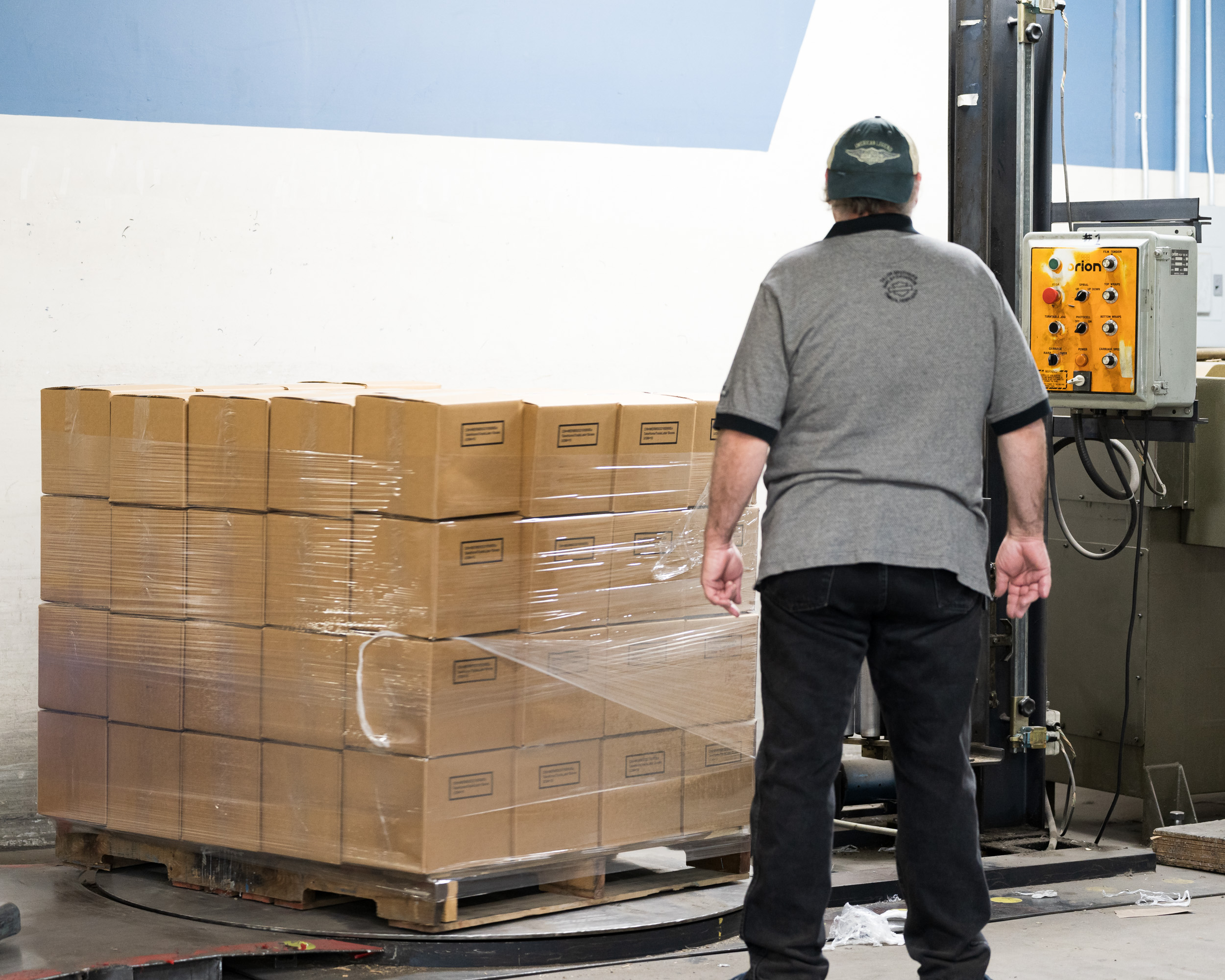 A worker shrink-wrapping a pallet of boxes