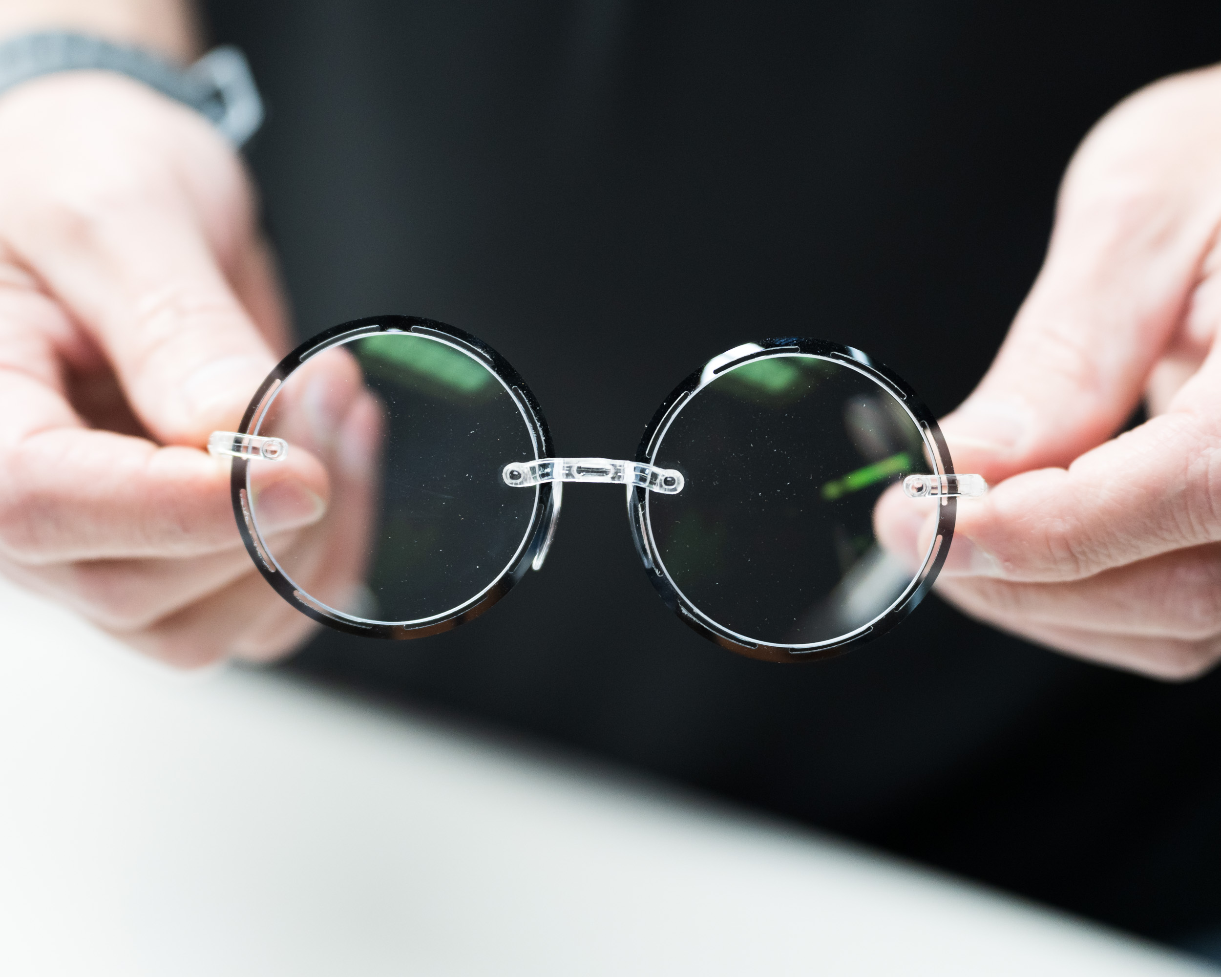 A person holding a pair of glasses